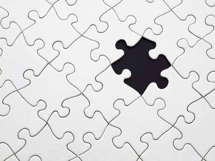 image of connected white puzzle pieces with one missing in the middle