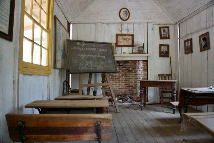 picture of 1800s classroom with blackboard, seats and a teacher's desk.